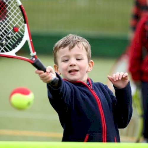 Young child hitting tennis ball